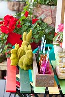 Detail of an inner city garden with three artificial grass rabbit ornaments, retro cement pots, recycled timber box with coloured glass bottles with drinking straws and colourful outdoor table and chairs.