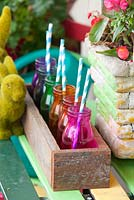 Detail of an inner city garden with artificial grass rabbit ornaments, retro cement pots, recycled timber box with coloured glass bottles with drinking straws and colourful outdoor table