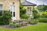Outdoor dining area on terrace next to victorian house. Half barrel tubs with box topiary balls, ivy and petunias.