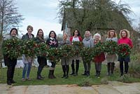 Christmas wreath making workshop. Francine and ladies with their completed wreaths featuring Hedera - Ivy, red sprayed fir cones, dried apples, Pinus - Christmas tree twigs, red twigs and Cinnamon sticks. December, St Francis Cottage