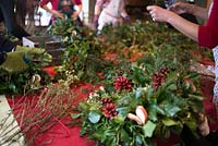 Christmas wreath making workshop.  The wreaths featuring Hedera - Ivy, red sprayed fir cones, dried apples, Pinus - Christmas tree twigs, red twigs and Cinnamon sticks. December, St Francis Cottage