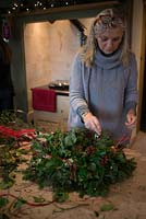Christmas wreath making workshop.  Lady completing a wreath featuring Hedera - Ivy, red sprayed fir cones, dried apples, Pinus - Christmas tree twigs, red twigs and Cinnamon sticks. December, St Francis Cottage