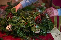 Christmas wreath making workshop. Wreath features Hedera - Ivy, red sprayed fir cones, dried apples, Pinus - Christmas tree twigs and Cinnamon sticks. December, St Francis Cottage