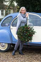 Christmas wreath making workshop. Lady by her vintage Citroen car with a completed wreath featuring Hedera - Ivy, red sprayed fir cones, dried apples, Pinus - Christmas tree twigs, red twigs and Cinnamon sticks.  December, St Francis Cottage