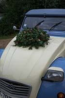 Christmas wreath making workshop. Completed wreath on a vintage Citroen car bonnet featuring Hedera - Ivy, red sprayed fir cones, dried apples, Pinus - Christmas tree twigs, red twigs and Cinnamon sticks. on her December, St Francis Cottage