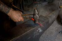Paul Gilbert, blacksmith and sculptor, in his workshop making leaf figure from metal rod