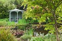 Waterlily Pond and gazebo, with Acer and Iris planting around the pond. Ellerker Manor, Ellerker, East Yorkshire. Spring, May 2016.