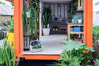 The Inside of a an orange shipping crate used as a potting shed at the RHS Greening Grey Britain for Health, Happiness and Horticulture Garden. RHS Chelsea Flower Show 2016 - Designer: Annie-Marie Powell