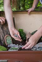 Add a gravel mulch to the compost once figurines and plants are in position