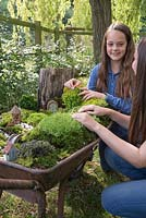 Miniature Wheelbarrow Garden. Two young girls building a miniature garden inside a wheelbarrow