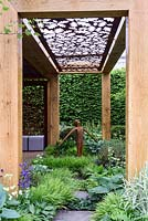 The Morgan Stanley garden for Great Ormond Street Hospital. Rusty metal stenciled screen above pergola walk in timber frame. Rusting metal figure of young boy in woodland garden. RHS Chelsea Flower Show 2016
