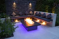 Secluded seating area with a dry stone slate wall and propane fire pit emitting blue light