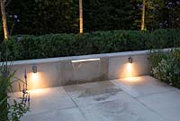 Downlight lighting on both sides of a water feature, with sunken borders either side