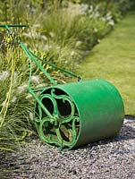 Old cast iron garden roller painted green, next to Croquet Lawn at RHS Rosemoor