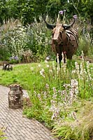 Macmillan Legacy Garden, Hampton Court Palace Flower Show 2014. Rusted metal cattle sculpture, brick path, informal flower meadow borders.