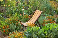 Deckchair in kitchen garden. Raised beds full of vegetables, herbs and flowers.
