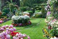 Colourful mixed beds filled shrubs, perennials and tender bedding plants, including Lobelia, Calendula, Begonia, Clematis, Achillea, Leucanthemum and Rosa with path across the lawn to pergola.