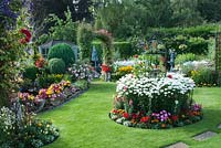 Colourful mixed beds filled shrubs, perennials and tender bedding plants, including Lobelia, Calendula, Begonia, Clematis, Achillea, Leucanthemum and Rosa.