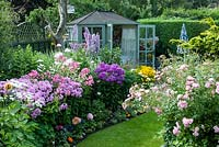Colourful back garden with mixed borders filled with tender bedding plants, shrubs and perennials including Rosa 'The Fairy', Delphinium 'Sweet Sensation', Phlox 'Elizabeth'