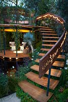Belvedere in the Winton Beauty of Mathematics Garden lit at night, RHS Chelsea Flower Show 2016. Illuminated mathematical symbols cut into band of copper to form bannister for staircase