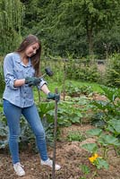 Girl using a rubber mallet to place a stake in a Pumpkin patch