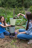 Two girls filling galvanised buckets with compost