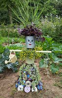 A scarecrow made from galvanised buckets, compact discs, wood and string. Plants included are Variegated Helichrysum, Iresine, Sanvitalia procumbens 'Sunvy Trailing' and Panicum virgatum 'Warrior'
