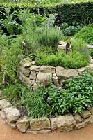Herb spiral made of stones with Mentha x piperita, Allium schoenoprasum, Satureja montana, Lavandula angustifolia and Rosmarinus officinalis. 'Le jardin qui se savoure' designed by Guillaume Popineau, David Trigolet and Chantal Dufour at the Festival International des Jardins 2016, Chaumont-sur-Loire, France