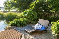 Next to the pond and wood deck, sun lounger on granite paved area backed by plants as Darmera peltata, Hedera arborescens and Quercus pontica