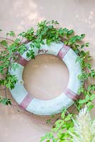 Decoration detail of a bathhouse wall. Life ring with clematis trendrils
