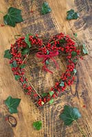 A wreath made from Ivy and Ilex aquifolium on wooden surface