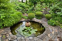 Circular pond with water lily and decorative urn.  Clipped box balls, relaxing area and borders. Frank Thuyls garden