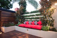 Inner city courtyard with raised garden bed bench seat with grey and red cushions. A brick wall with Trachelospermum jasminoides and Star jasmine