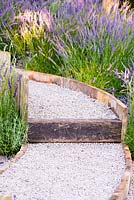 Raised gravel path separated with natural wooden bars surrounded by Lavender - Lavandula x intermedia 'Grosso'. The Lavender Garden, Designers: Paula Napper, Sara Warren, Donna King, Sponsor: Shropshire Lavender. RHS Hampton Court Flower Show 2016