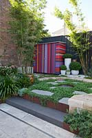 View of garden with colourful striped shed, ground covers include echeveria, Scaevola aemula - native fan flower, Viola hederacea - Australian native violet, Crassula ovata 'Gollum' and bamboo in the background. Step has corten steel edging.