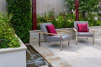 A pair of grey padded stainless steel Barlow Tyrie Equinox' Armchairs  with burgundy cushions and pergola on Yorkstone paved terrace, surrounded by raised beds. Plants include Achillea millefolium 'Paprika', Pennisetum orientale, Penstemon 'Port Wine', Sanguisorba 'Chocolate Tip' and Taxus baccata.  Squire's 80th Anniversary Garden, RHS Hampton Court Flower Show 2016. Designer: Catherine MacDonald - Sponsor: Squire's Garden Centres