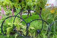 Bicycle wheels used as boundary fencing. with  Vitis vinifera, Helenium 'Wyndley', and Achillea 'Apricot Delight'. Great Gardens of the USA: The Oregon Garden, RHS Hampton Court Flower Show in 2016