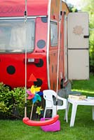 Swing in a childrens playground with a Ladybird trailer.
