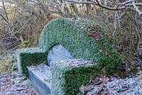 Seat in the Magnolia Walk. Clipped hedge of Buxus sempervirens. Veddw House Garden, Monmouthshire, Wales, UK. November. Garden designed and created by Anne Wareham and Charles Hawes