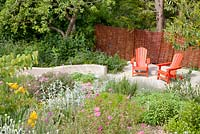 Decorative painted red garden seats on patio with Cistus, Iris and Stachys