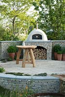 Outdoor pizza oven surrounded by pots of herbs,  with table and Cow Parsley in a jug - The Refuge Garden in aid of Help Refugees UK, RHS Malvern Spring Festival 2017 - Design: Sue Jollans, Sponsors: Readyhedge, Everedge, Outchester and Ross Farm Cottages