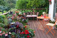 Decorative bright orange garden furniture on decked terrace with colourful summer containers. Patio garden. Owner: Pattie Barron