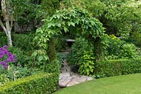 An arch covered with Virginia creeper, Parthenocissus quinquefolia, above a stone path leading to a secluded bench.