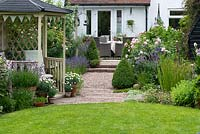A gazebo is placed a third of the way down a 24m x 7.6m town garden. Above, a rising pebble path lined in lavender and roses leads to a terrace
