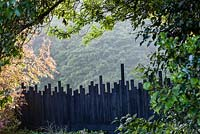 Irregular fence of black painted battening. Veddw House Garden, Monmouthshire, Wales. May. Garden designed and created by Anne Wareham and Charles Hawes