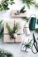 Wrapped presents using brown paper and string with reels of string, decorated with greenery from fir tree foliage and yew tree with half dipped pine cones