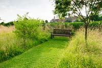 Paths are mown between long meadow grasses, here giving access to a wooden bench.  Felley Priory, Underwood, Notts, UK