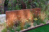 Brownfield - Metamorposis. Planting in gravel bed with the backing of large steel structure, Achillea and grasses, Design: Martyn Wilson. Sponsors: St. Modwen. RHS Hampton Court Palace Flower Show 2017