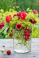 Summer floral arrangement in glass jar with red sweetpeas, potentialla, fragaria vesca, red currants and alchemilla mollis