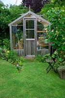 Garden view with wooden greenhouse and vegetable bed